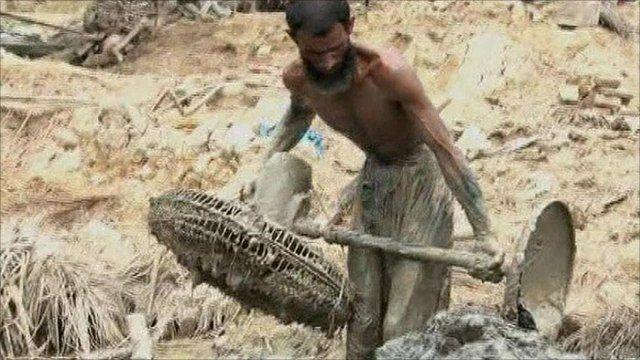 Pakistani man lifting mud-coated fan