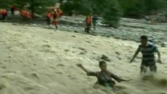 A reporter is swept away by the flood water