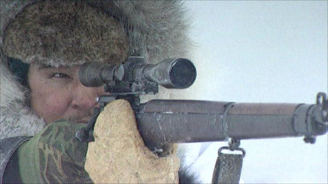 A Canadian Inuit aims at a seal
