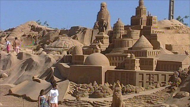 Couple walking past giant sand sculpture