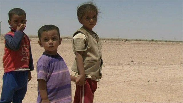 Syrian children stand in a dusty field