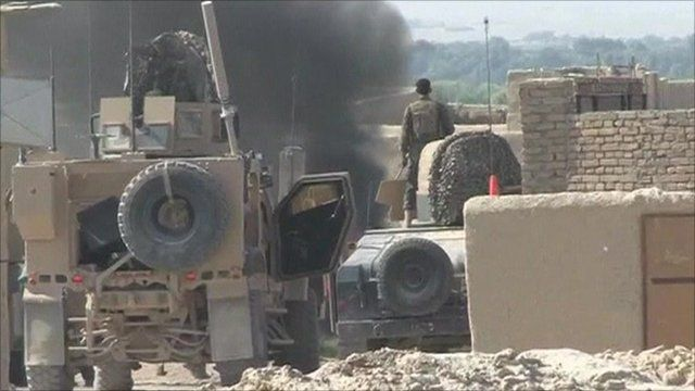 Military vehicle with smoke in background