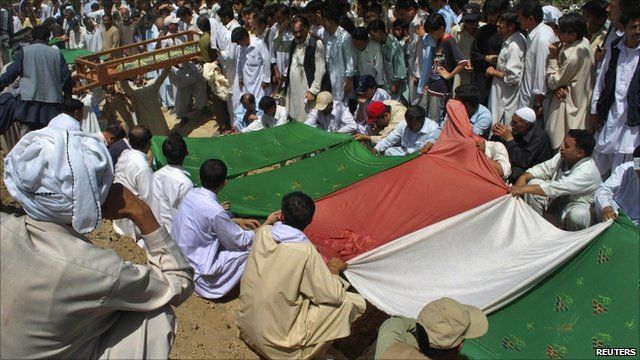 Shia Muslims cover the graves of some of Quetta attack victims