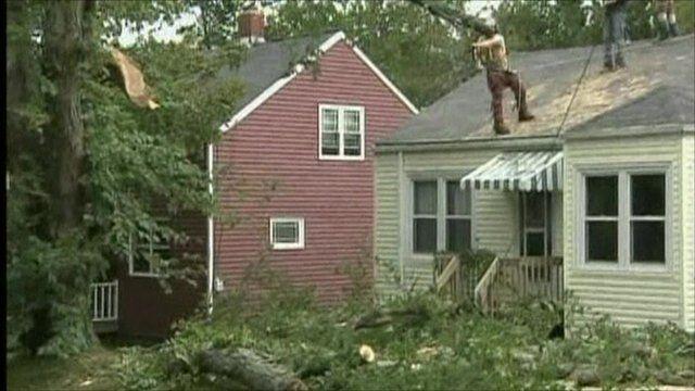 man cuts down trees near house