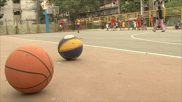 Children playing basketball on court