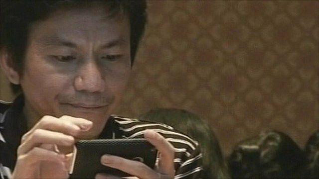 A Thai man tries out a 3G phone