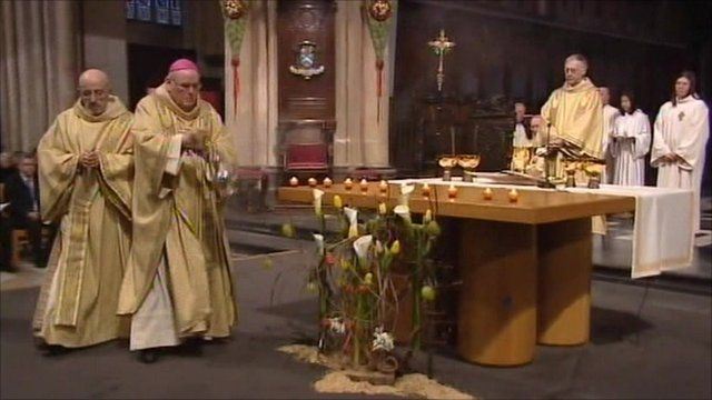 Priests holding candles in church