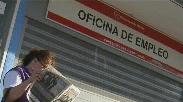 Woman reading paper outside Spanish job centre