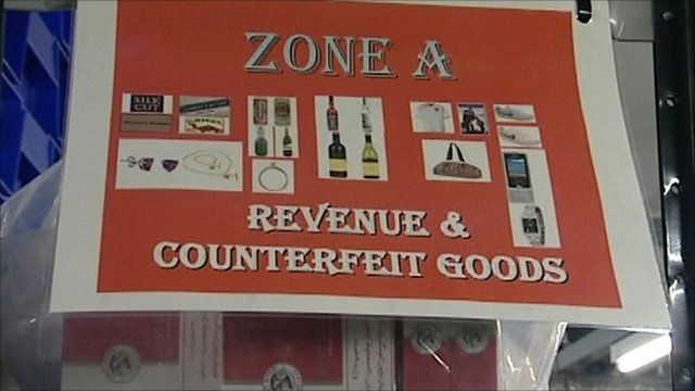 Sign on shelves fuill of counterfeit goods