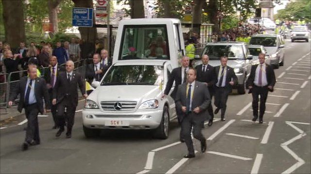 Popemobile surrounded by security men