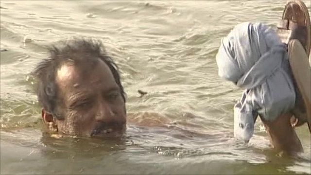 Pakistani man swimming in flood waters