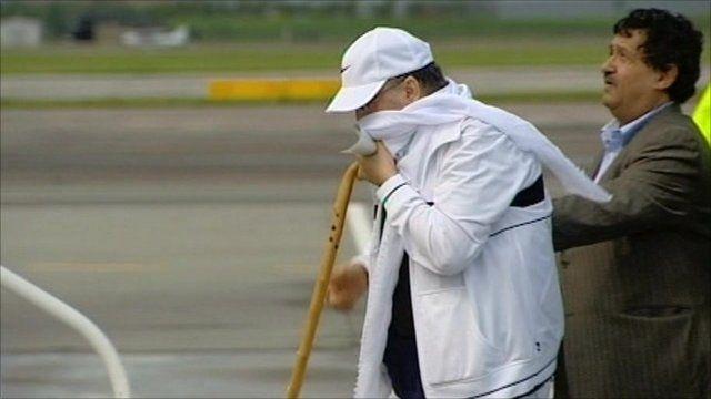 Abdelbasset al-Megrahi being helped off a plane