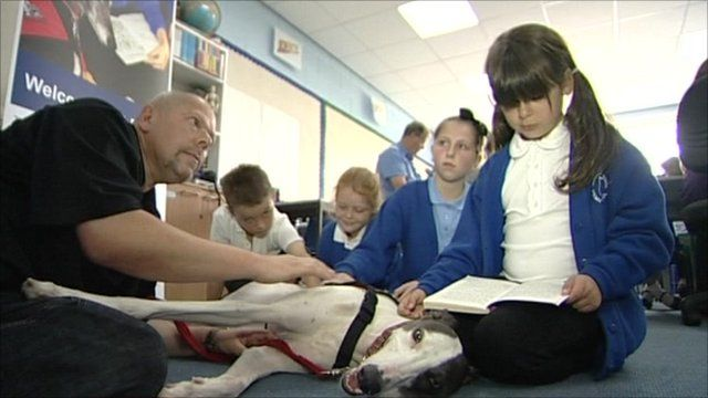Dog helps children read in a classroom