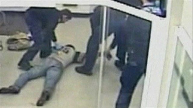 Man lies on floor as police hold his arm