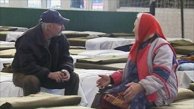 Couple sit on beds in rescue centre