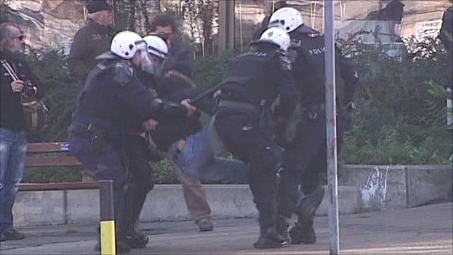 Police in Belgrade tackle a protestor