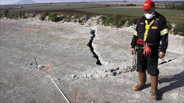 Worker stands next to crack