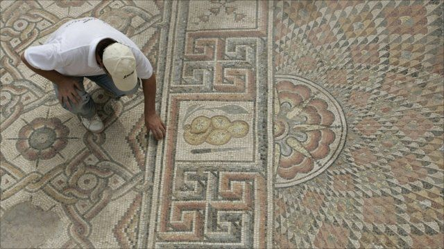 Man examines mosaic
