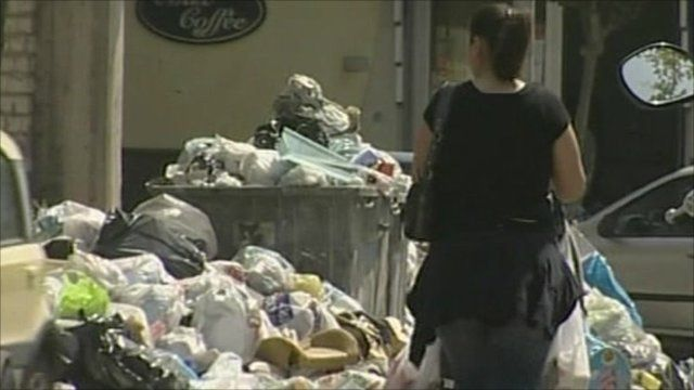 Woman walks past pile of rubbish