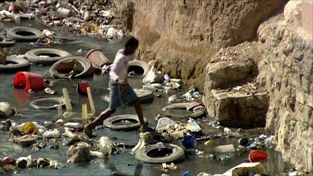 Child crossing infected stream in Haiti