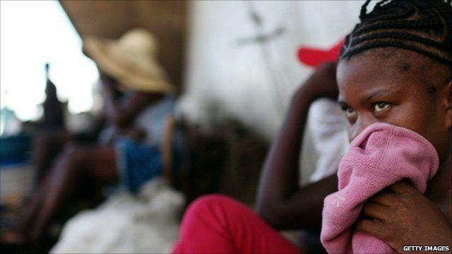 Woman in Haiti shielding her face