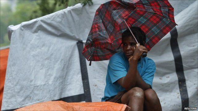 Woman sheltering under broken umbrella