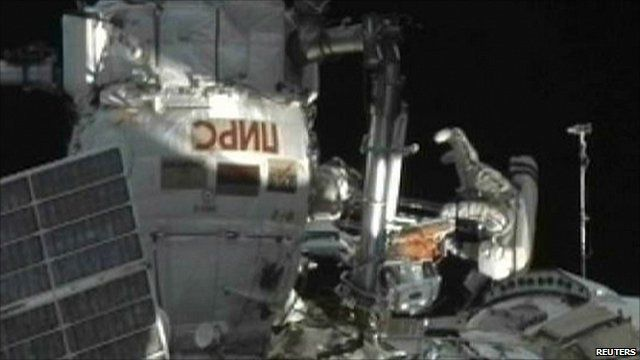 Russian cosmonaut Oleg Skripochka (upside down) emerging from ISS