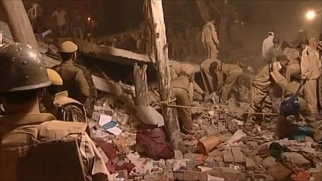Emergency workers sort through rubble