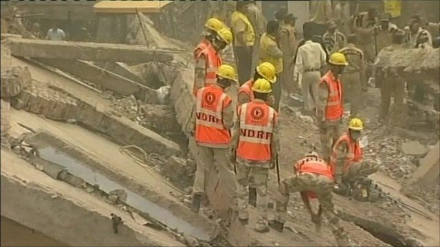 Rescuers search through rubble of collapsed building
