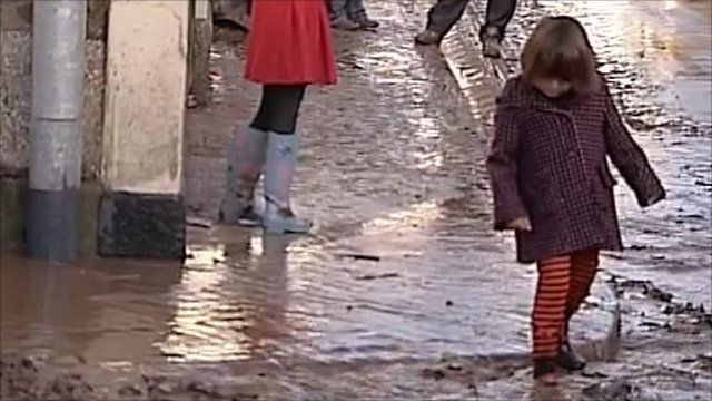 A child tests the floodwaters