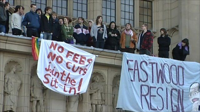 Students protesting on the balcony of a university building with banners