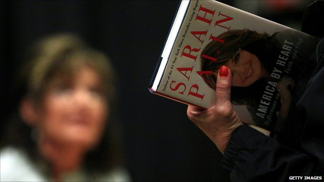 Customer holding copy of Sarah Palin's book in front of Ms Palin