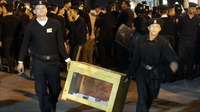 Police officers carry ballot box in Cairo