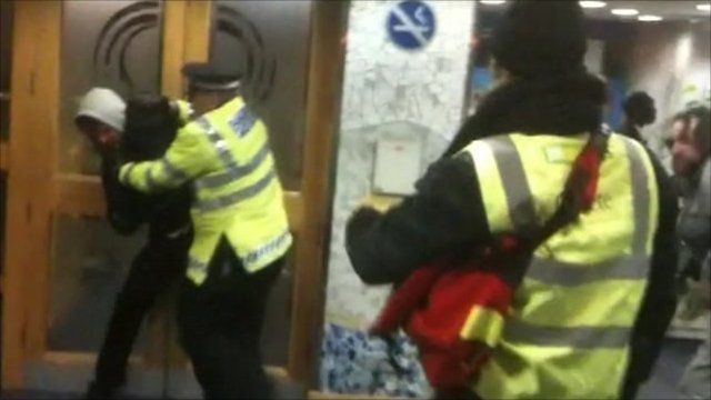 Security guard apprehends a protester who has entered the building