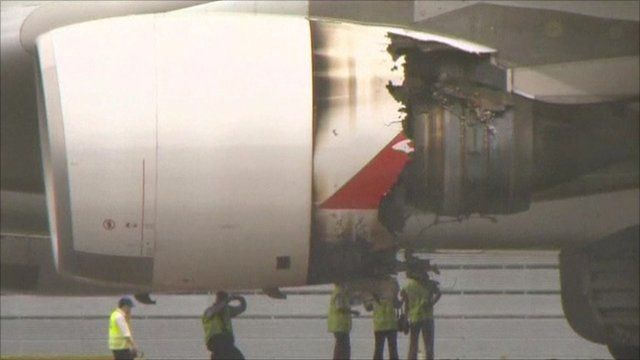 Engineers survey the damage to the Qantas A-380 engine