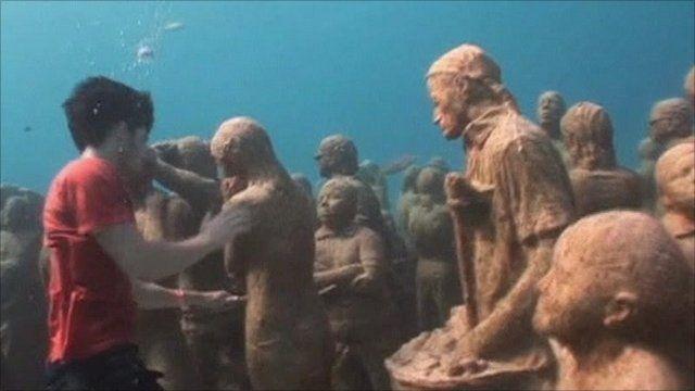 Greenpeace activist underwater with human sculptures