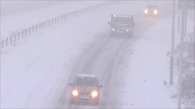 Cars drive through snow on the A465 in Wales