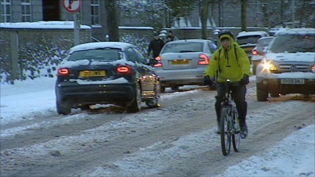 Cars and a cyclist on a snow covered road in Aberdeen