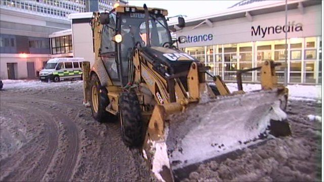 Tractor clearing snow from the front of a hospital