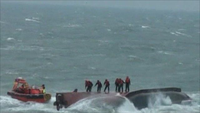 Passengers standing on the capsized boat