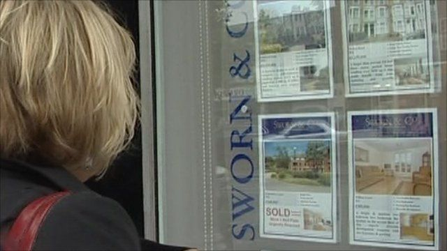 Woman looking in estate agents' window