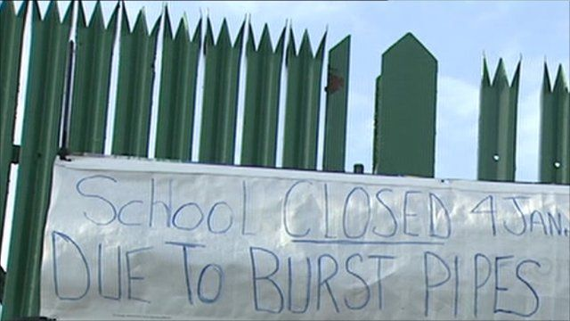 A sign on a school gate saying the school is closed due to flooding