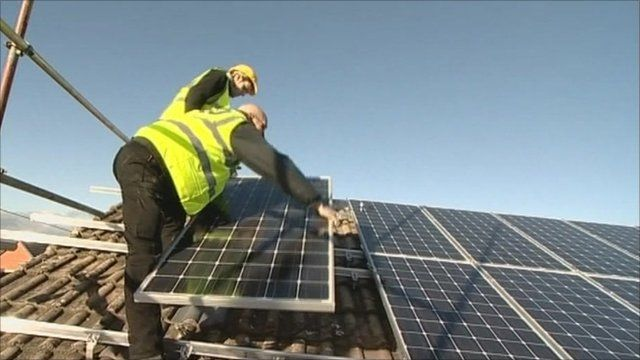 Men installing solar panels to a roof