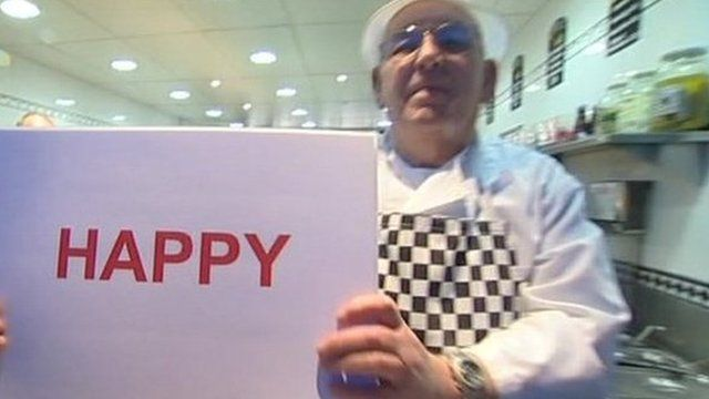 Man holding a happy sign