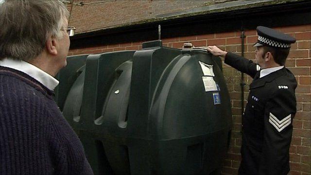 A police officer checks a heating oil tank