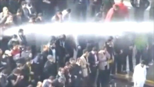 Protesters pray in front of water cannon