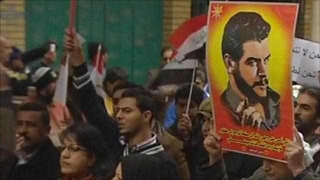 An Iraqi protester holds a poster of Che Guevara