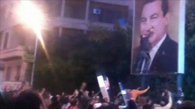 Protesters attack a poster of President Mubarak