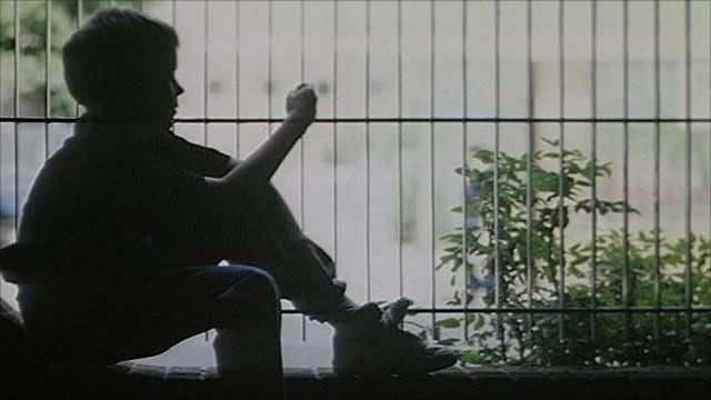 A teenage boy sitting in front of a metal fence