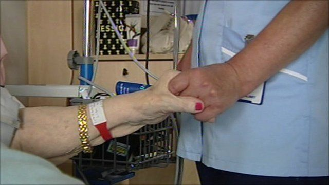A nurse holds an elderly patient's hand